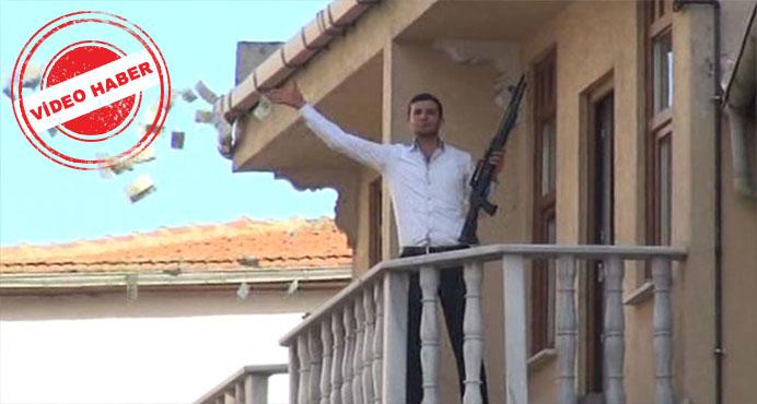 Elinde silahla, balkondan para saçıyor